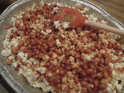 Pour hot caramel over the preheated popcorn and peanuts.